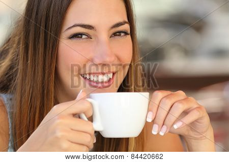 Woman Tasting A Coffee From A Cup In A Restaurant Terrace