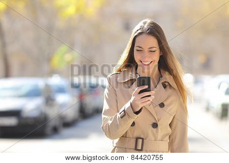 Woman Walking And Using A Smart Phone On The Street