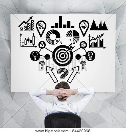 Businessman Looking At  Analitics Scheme