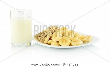 Macro Shot Slices Banana On Plate With Glass Of Milk On White