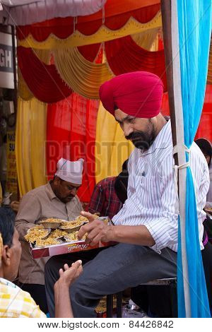 Delhi, India - November 5: Unidentified Man Gives Away Rice During Guru Nanak Gurpurab Celebration O