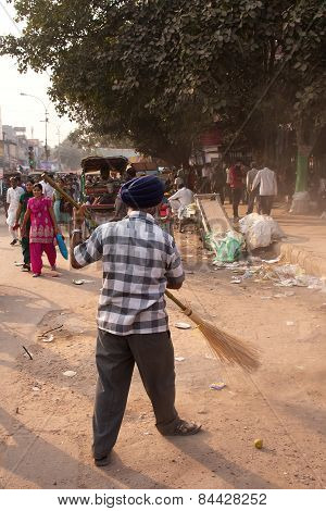 Delhi, India - November 5: Unidentified Man Cleans Street After Guru Nanak Gurpurab Celebration On N