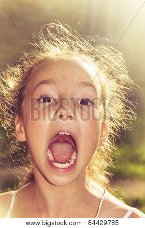 Shouting loud little girl at sunset