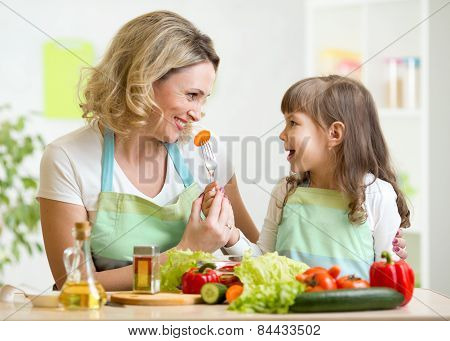 kid feeding mother vegetables in kitchen