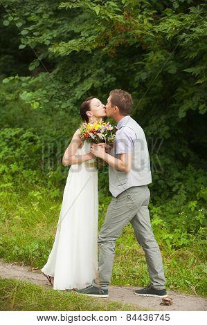 happy bride groom standing in green park, kissing