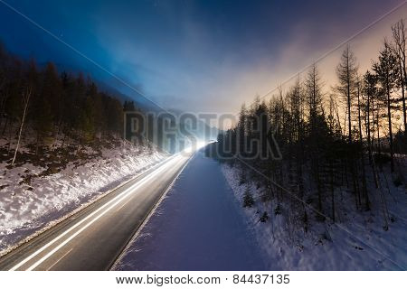 car light tracks on street at winter night with colorful sky