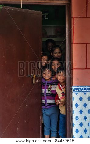 Children Look Out Behind The Door