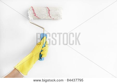 Woman painting wall with roller brush.