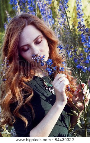 Sensual Redheaded Woman In Sunset Light Smelling Flowers