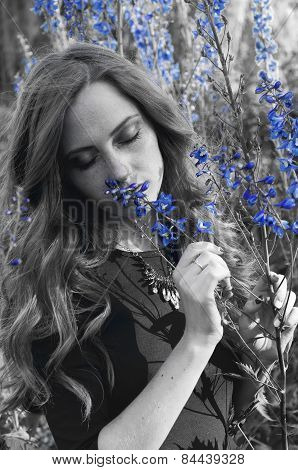 Sensual Redheaded Woman In Sunset Light Smelling Aconite Flowers