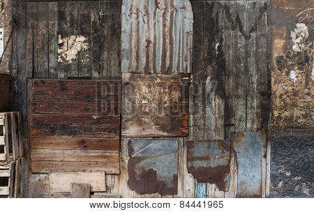 Old dark brown wooden and tin vintage wall or fence background.