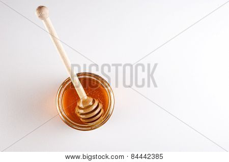 Glass Can Full Of Honey And Wooden Stick In It. Top View