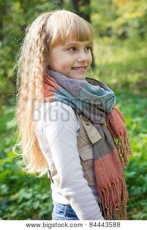 Beautiful little young baby stands in a scarf. Lovely child smiling