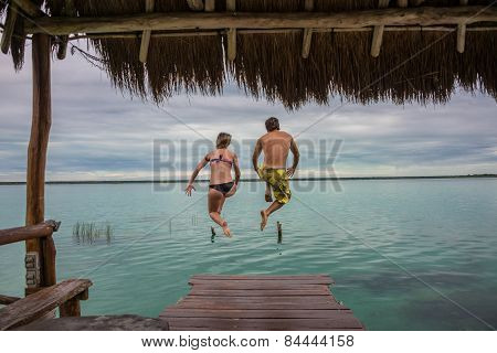 Beautiful Couple In Love Jumping And Having Fun Bacalar Lake. Riviera Maya, Mexico. Tropical Travel.