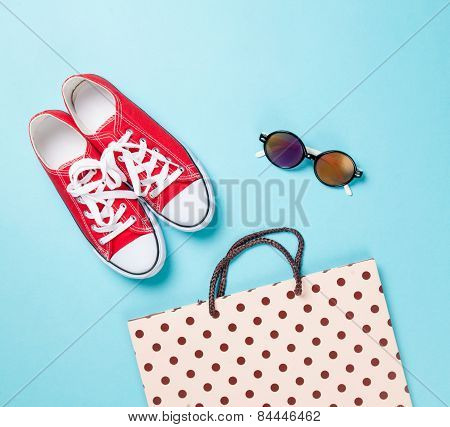 Red Gumshoes With Shpping Bags And Sunglasses