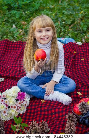 Beautiful little young baby in a pink hat with an apple in his hand. Beautiful child sitting on a re