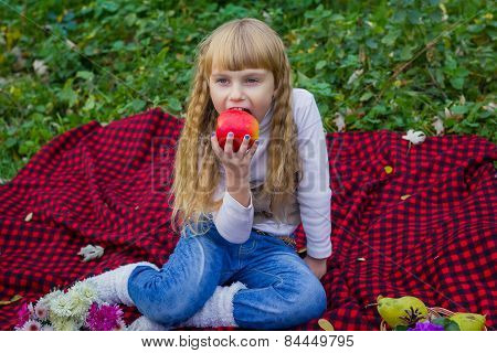 Beautiful little young baby in a pink hat with an apple in his hand. Beautiful child sitting