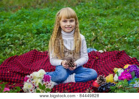 Beautiful little young baby in a pink hat with a lump in his hands. Beautiful child sitting on a red
