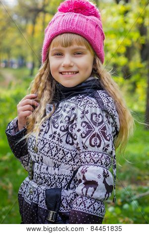 Adorable little blond girl with long blond hair in autumn park. Beautiful little young baby