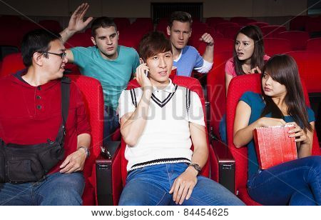 Young Men Talking On The Phone While Watching Movie At The Cinema