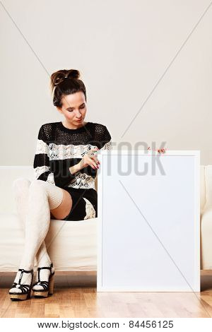 Woman On Sofa Holding Blank Presentation Board.