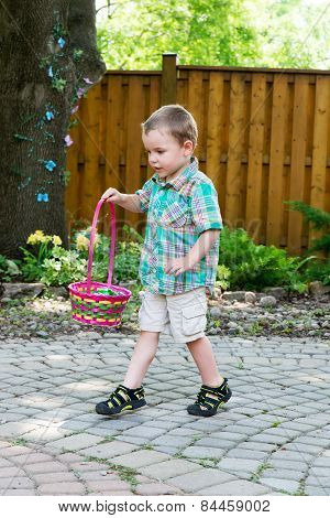 A cute boy holds a colorful Easter basket full of eggs