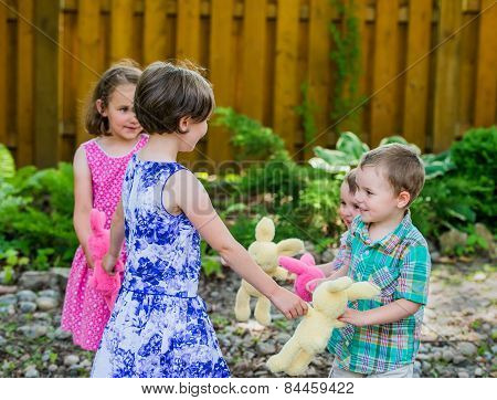 Two Girls And Two Boys Playing Ring Around The Rosie