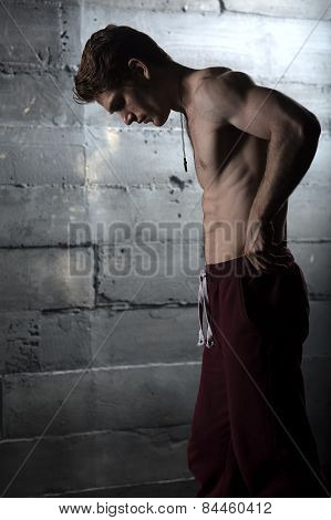 Handsome athlete with a naked torso adjusts his pants. The pictu