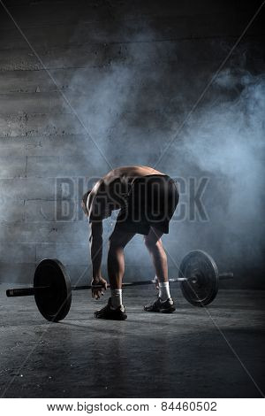 Portrait of a handsome athlete from behind. Athlete leaned over