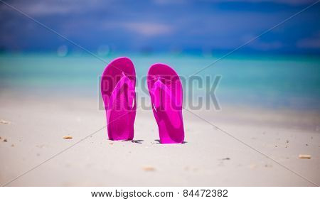 Pink vibrant beach flip flops on white sand on sea background