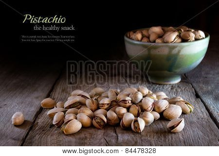 Pistachios In A Ceramic Bowl And On Rustic Wood, Dark Background
