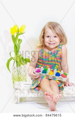 Little girl with Easter colored eggs in arms