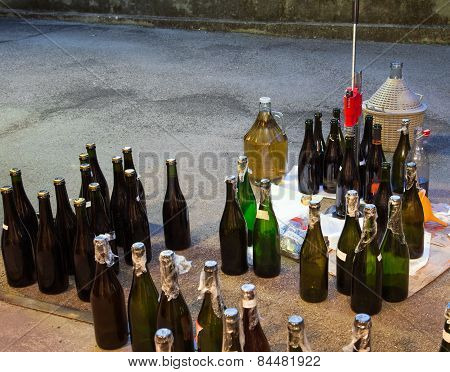 Pour The Wine In The Backyard With The Carboy And Bottles
