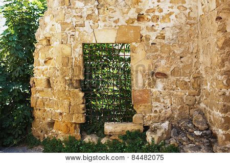 Old abandoned stone house ruins. North Cyprus. Door with metal grid.