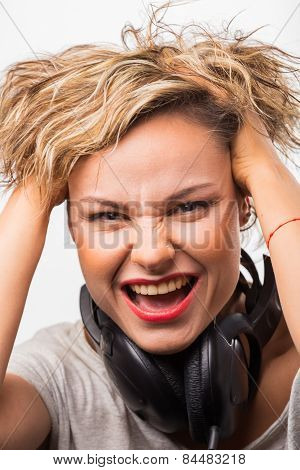 Cute blonde girl posing in the studio headphones