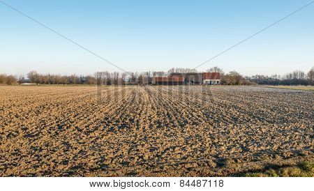 Plowed Field And A Farm