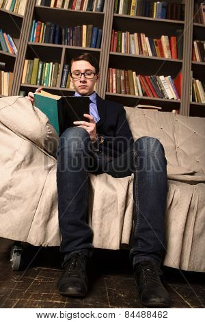 Old-fashioned Young Man Is Sitting In A Library And Reading A Book.