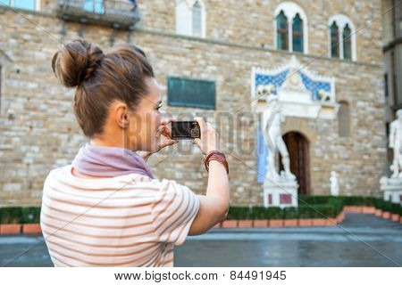 Closeup On Young Woman Taking Photo Of Palazzo Vecchio In Floren