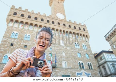 Portrait Of Happy Young Woman With Photo Camera In Front Of Pala