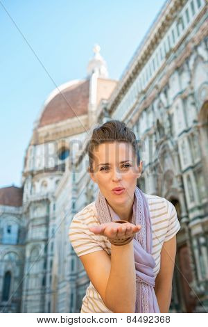 Portrait Of Happy Young Woman Blowing Kiss In Front Of Cattedrale Di Santa Maria Del Fiore In Floren