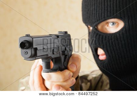 Man In Black Mask Holding Gun Before Him