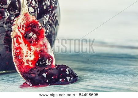 Close up of thick sweet strawberry jam with old spoon.