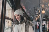 foto of tram  - Beautiful young woman wearing ecological fur poses on a tram - JPG