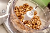 foto of food processor  - Kernel walnuts in a food processor ready to be crushed for prepare dessert - JPG