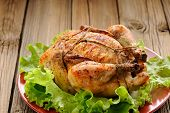 foto of bondage  - Bondage shibari roasted chicken with salad leaves on red plate on wooden background closeup horizontal - JPG