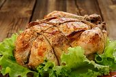 picture of bondage  - Bondage shibari roasted chicken with salad leaves on red plate on wooden background closeup horizontal - JPG