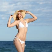 pic of sunbathing woman  - Perfect fitness woman body posing on the beach with the sea in the background - JPG