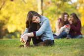 stock photo of knee  - Lonely girl leaning on knee in front of teenagers talking - JPG