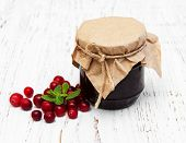 picture of jar jelly  - jar of cranberry jam with fresh fruits on a old wooden background - JPG