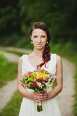 pic of bouquet  - Young woman with bouquet of flowers in her hands standing in green summer park - JPG